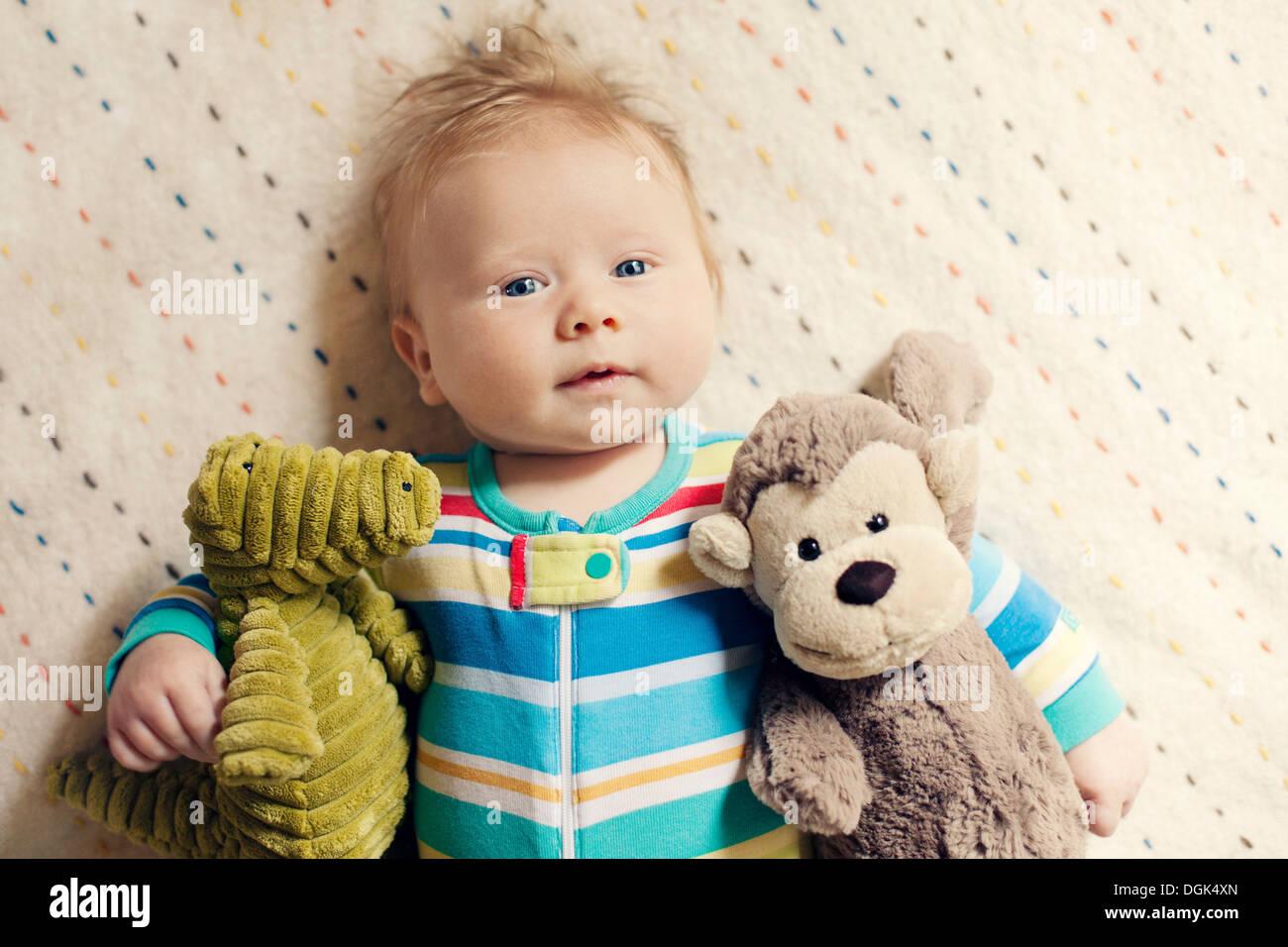 Baby boy cuddling soft toys - Stock Image