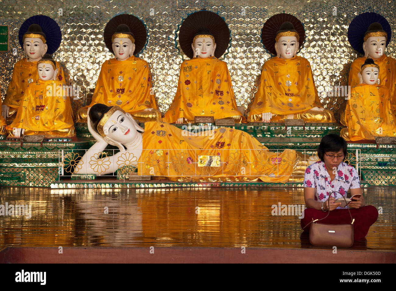 A woman reading sutras in front of an array of robed Buddhas at the Shwedagon Pagoda in Yangon in Myanmar. - Stock Image