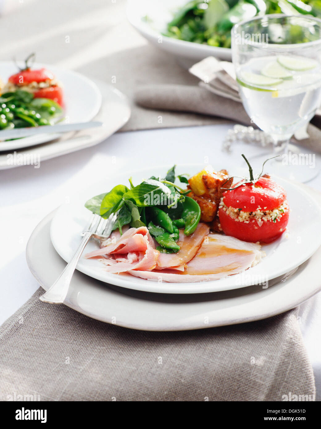Plates of glazed ham with stuffed tomatoes and spinach - Stock Image