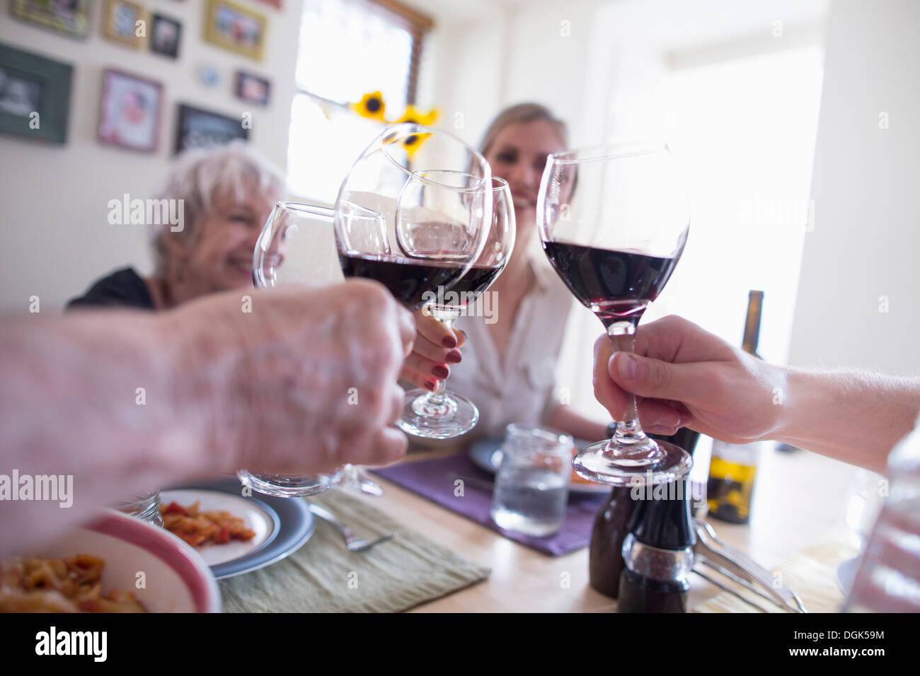 Family toasting with red wine at dinner table - Stock Image