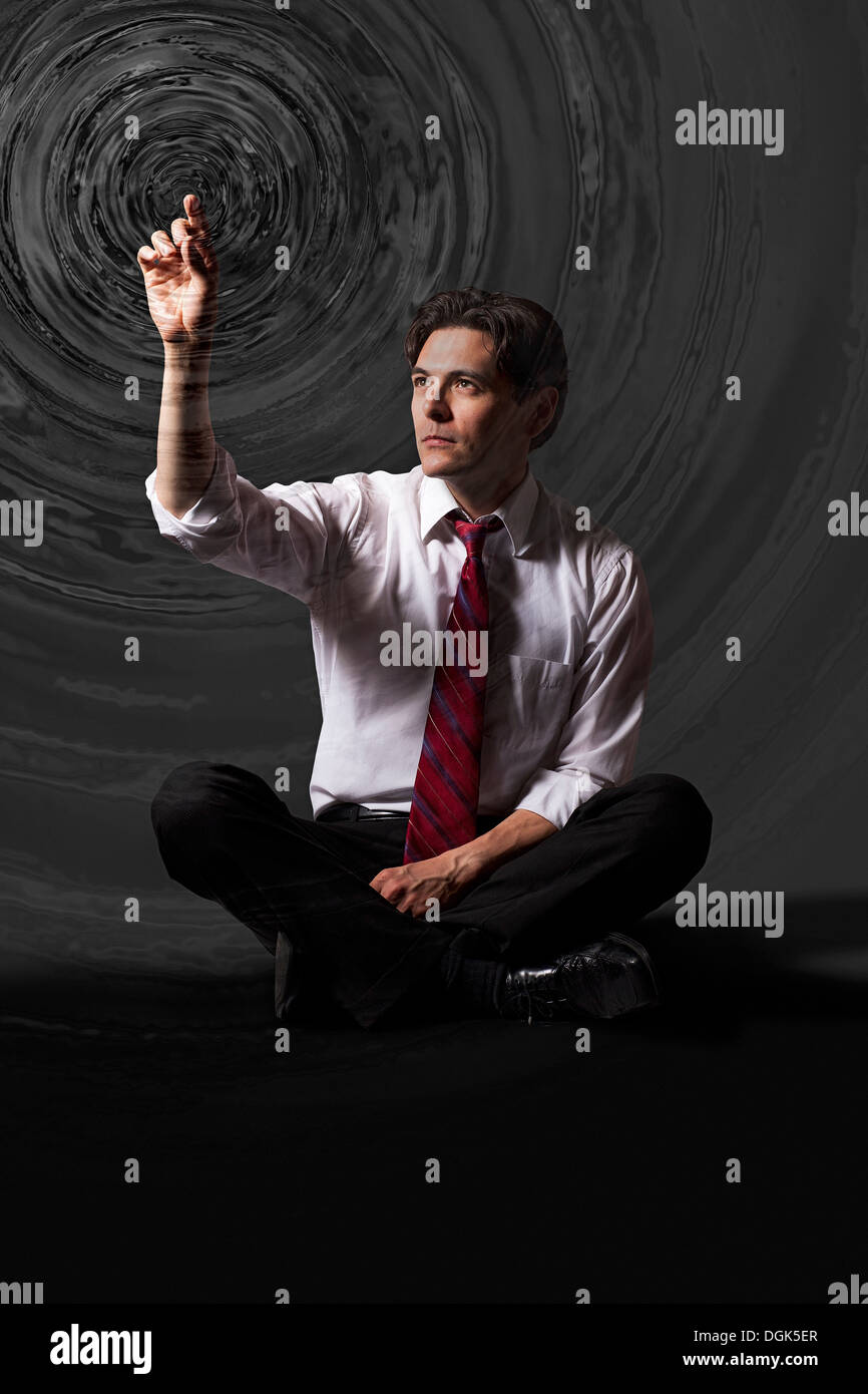 Businessman touching water ripple circles the air - Stock Image