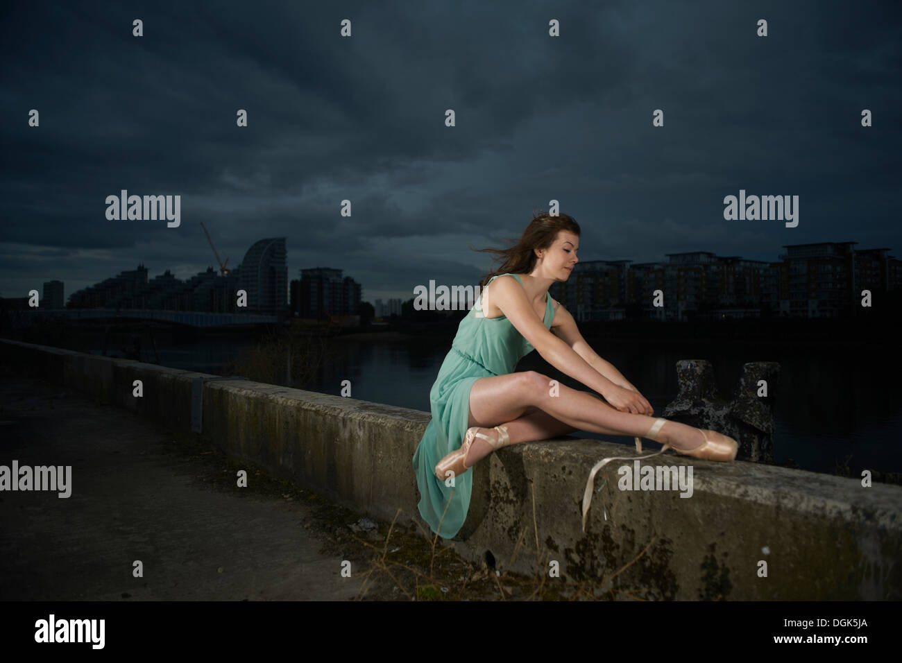 Ballet dancer sitting on wall - Stock Image