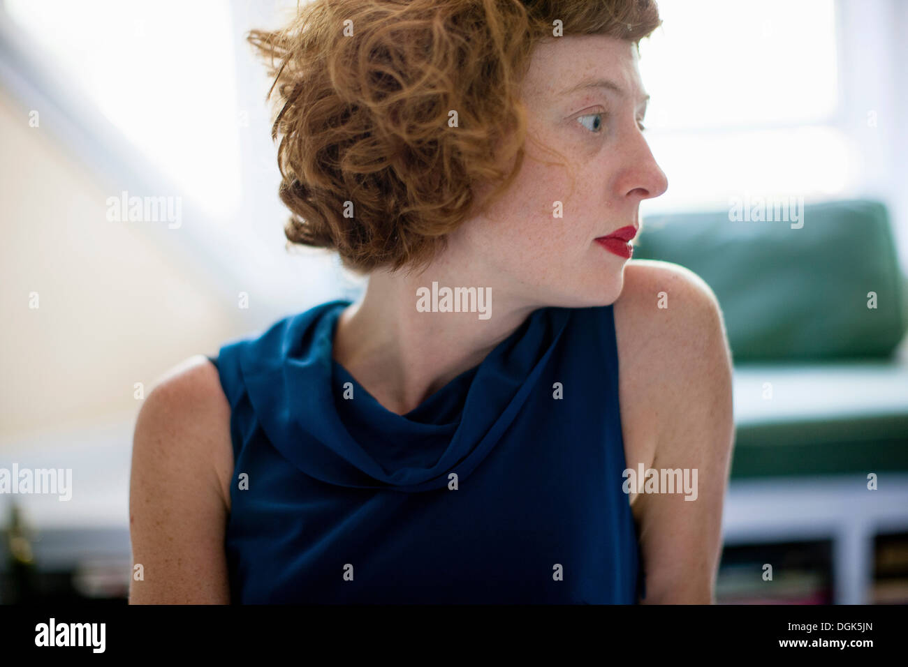 Close up profile of woman in sitting room - Stock Image
