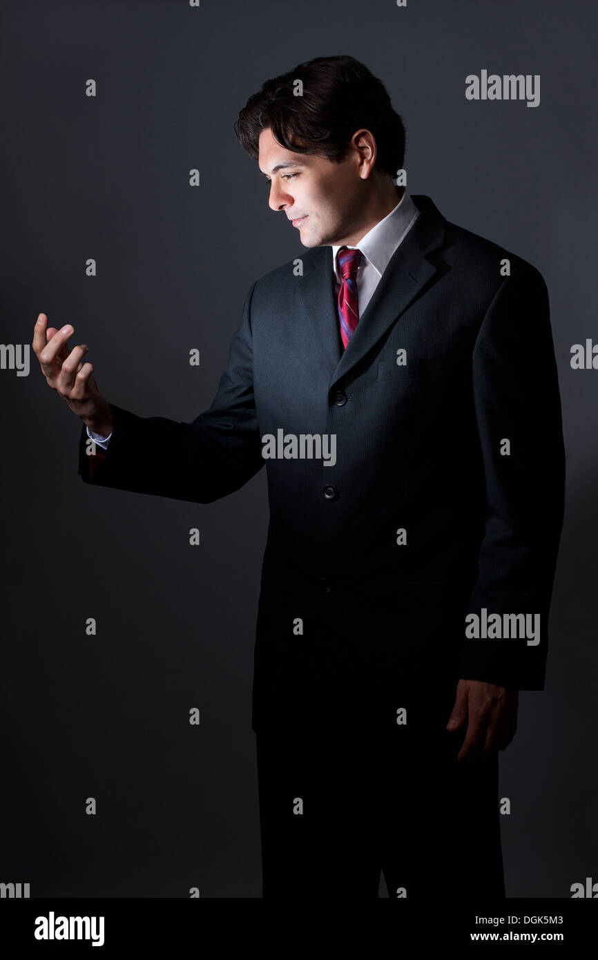 Businessman looking at hand as if holding cellphone, illuminated Stock Photo