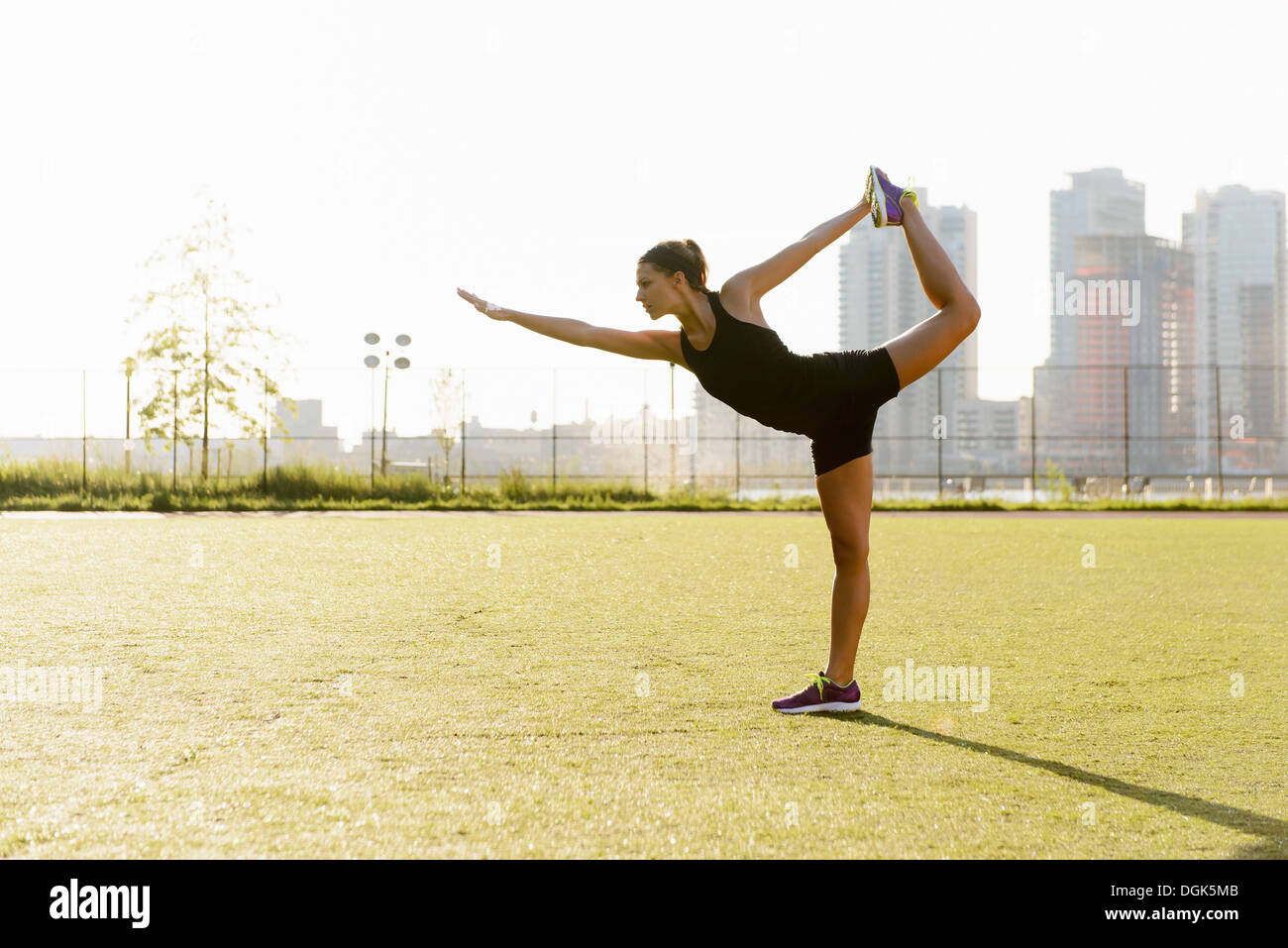 Young female doing yoga stretch in city park - Stock Image