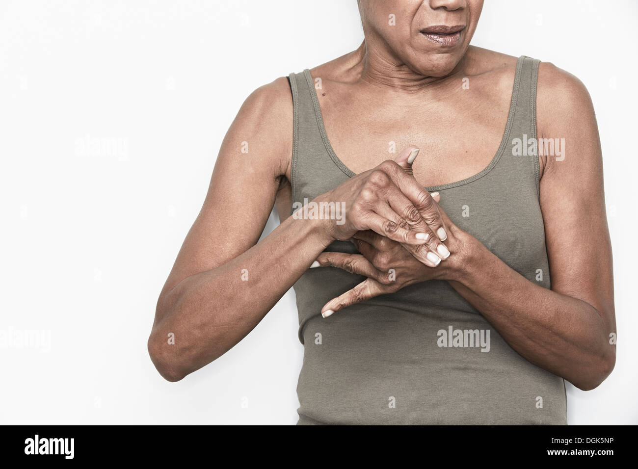 Cropped portrait of senior woman with hands clasped - Stock Image