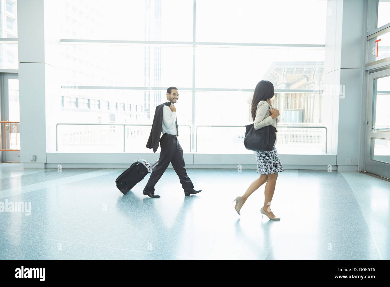Businesspeople walking through Staten Island Ferry terminal pulling wheeled suitcase - Stock Image