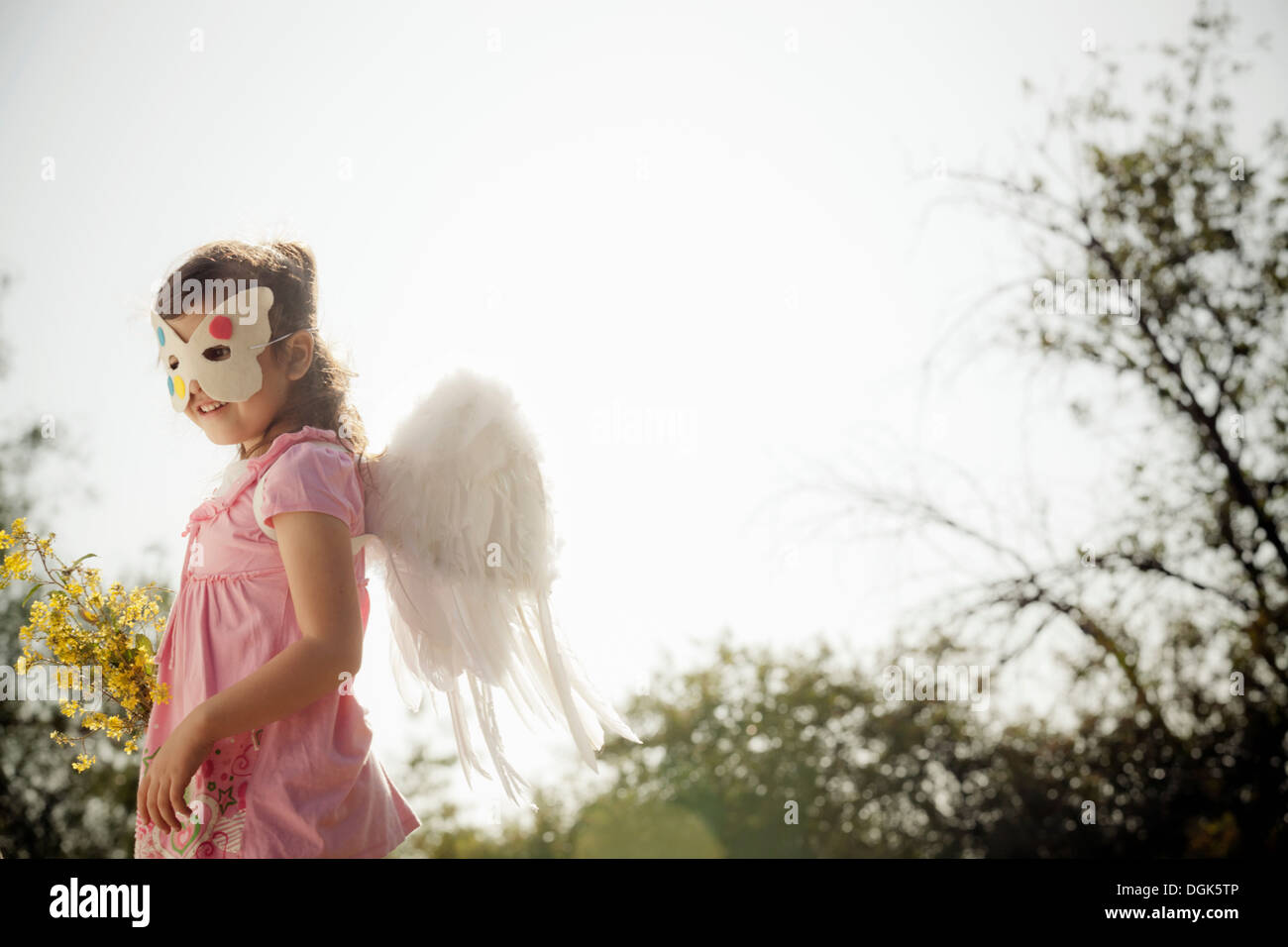 Girl in angel wings and face mask - Stock Image