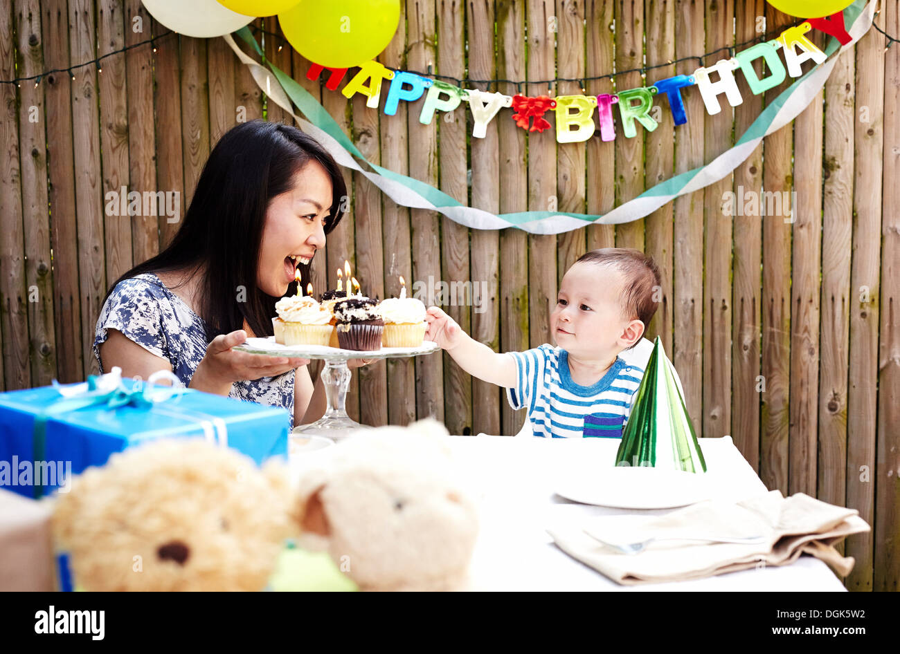 Mother showing cakes to baby boy - Stock Image