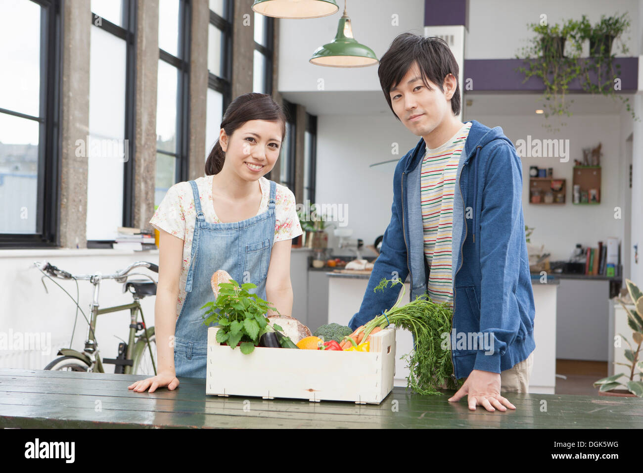 Portrait of young couple in kitchen with box of vegetables - Stock Image