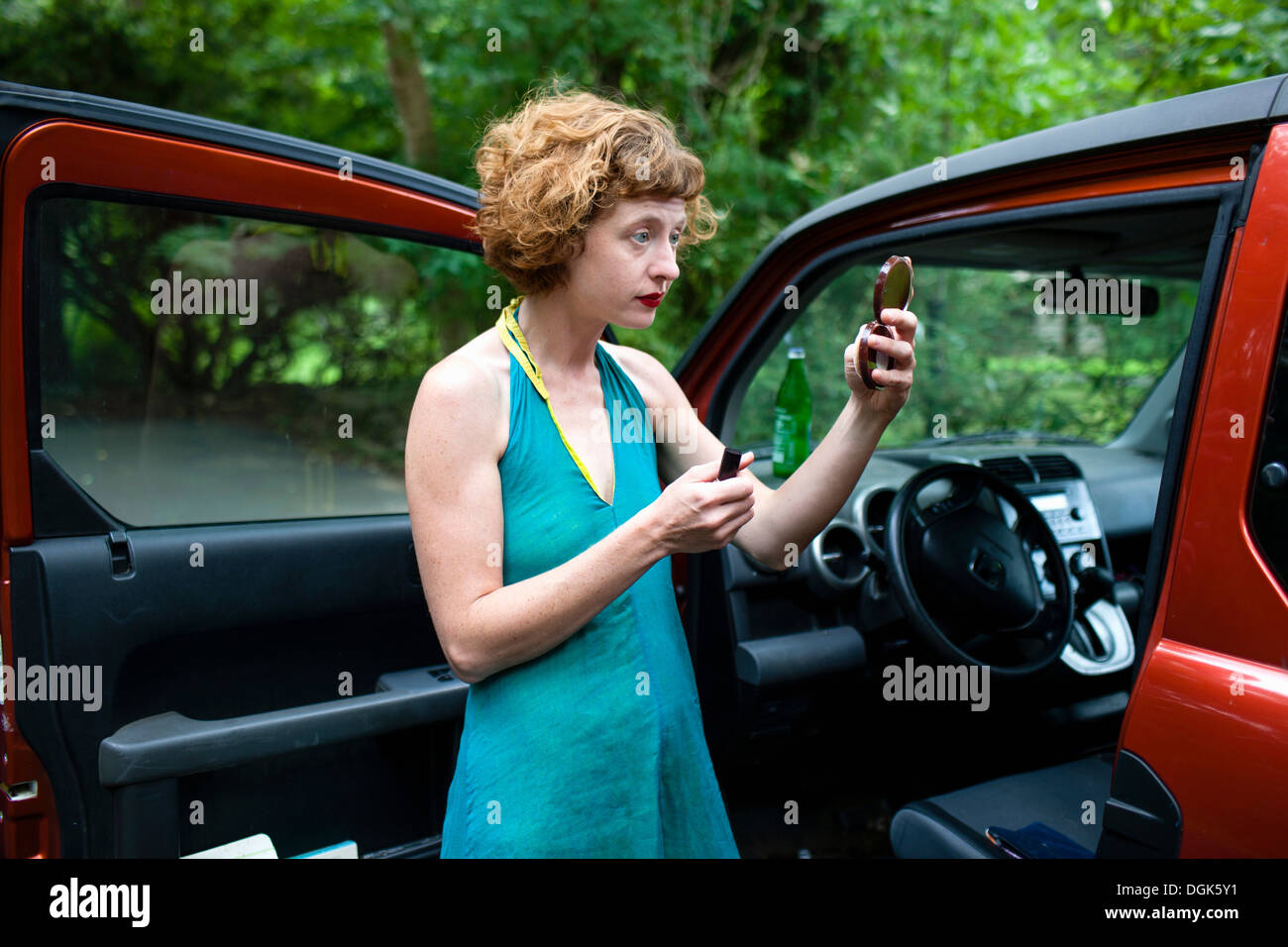Woman in forest looking at compact mirror - Stock Image