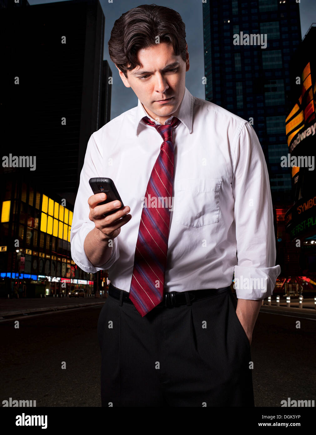 Stressed businessman in city with smartphone - Stock Image