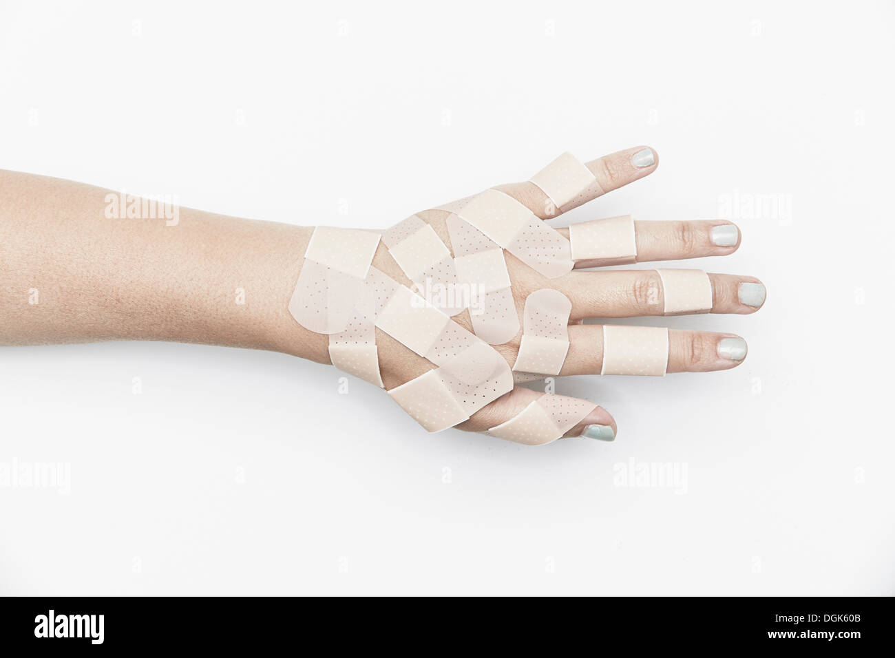 Cropped hand covered with adhesive plasters - Stock Image