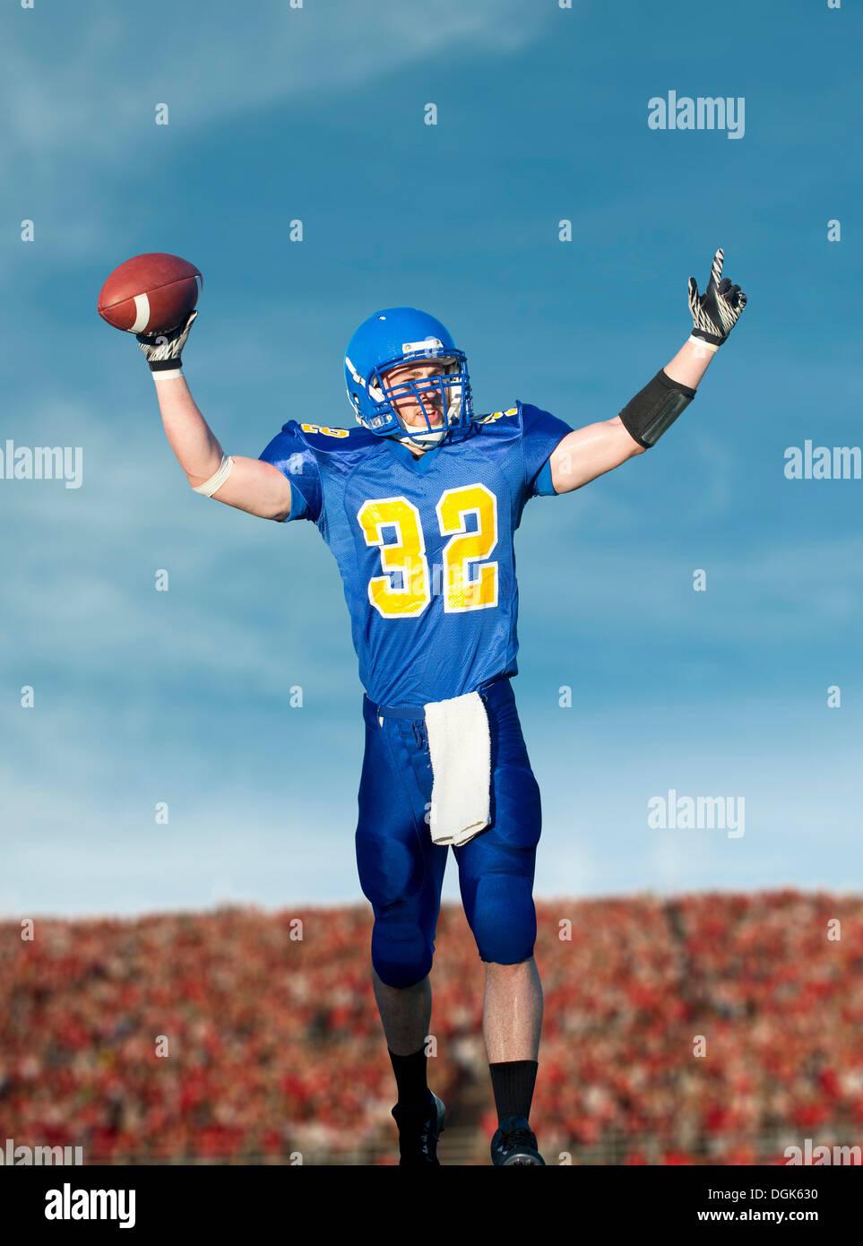 American footballer holding ball - Stock Image