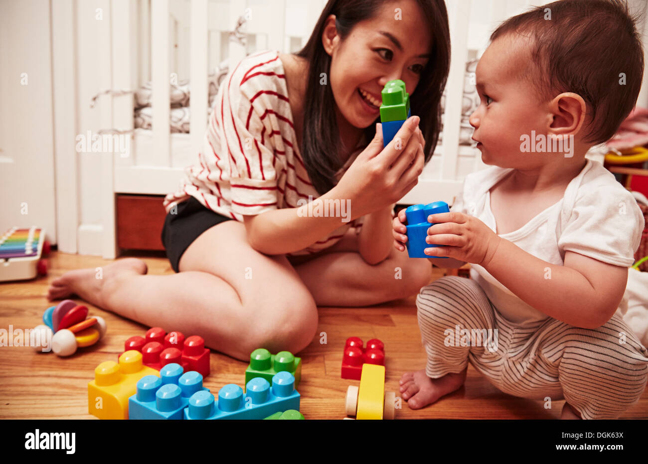 Mother and baby boy playing with building blocks - Stock Image