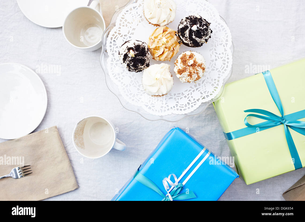 High level view of cupcakes, birthday presents and crockery - Stock Image