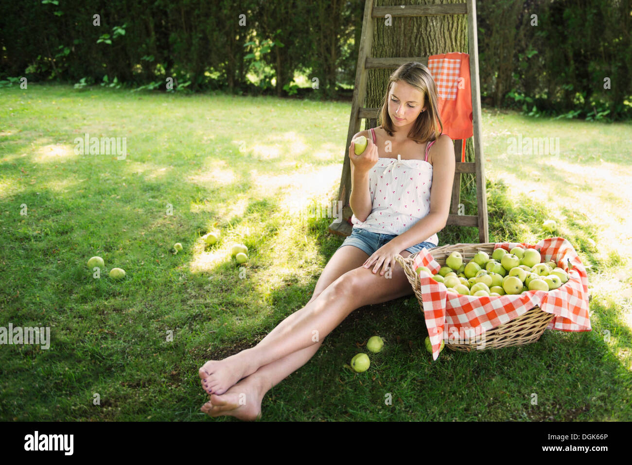 Adolescent girl sitting in orchard eating an apple Stock Photo