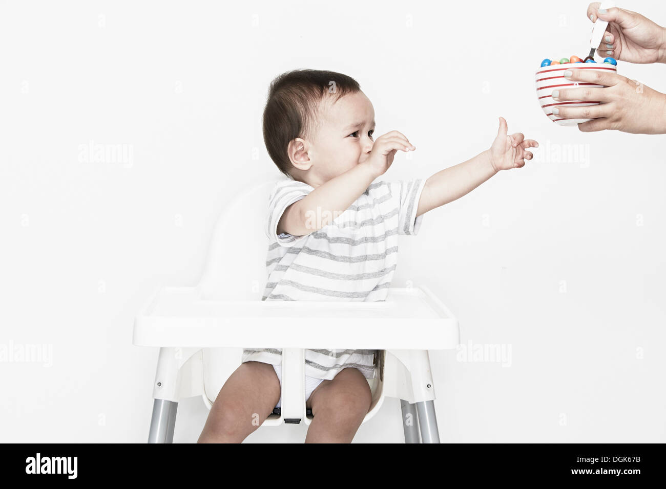 Baby boy sitting in highchair reaching for food - Stock Image