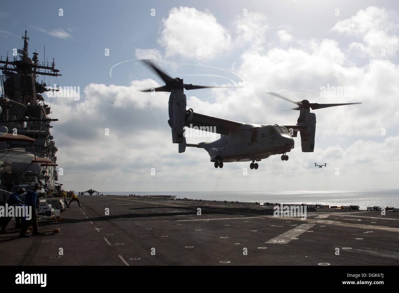An MV-22 Osprey from Marine Medium Tiltrotor Squadron (VMM) 266 (Reinforced) lands on the flight deck of the amphibious Stock Photo