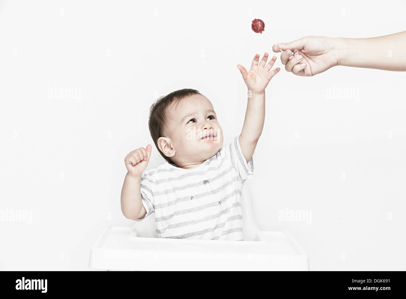 Baby boy reaching for lollipop - Stock Image