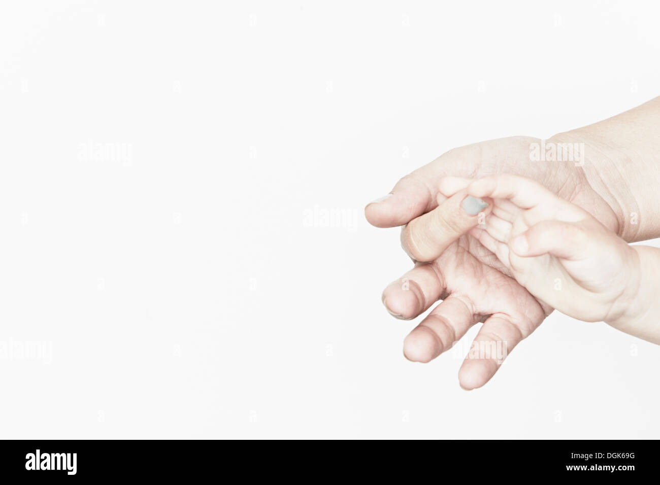 Baby's hand clasping mother's finger - Stock Image