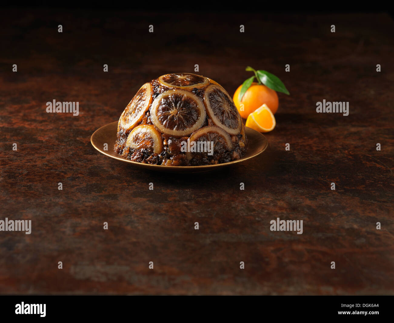 Christmas pudding decorated with sliced oranges - Stock Image