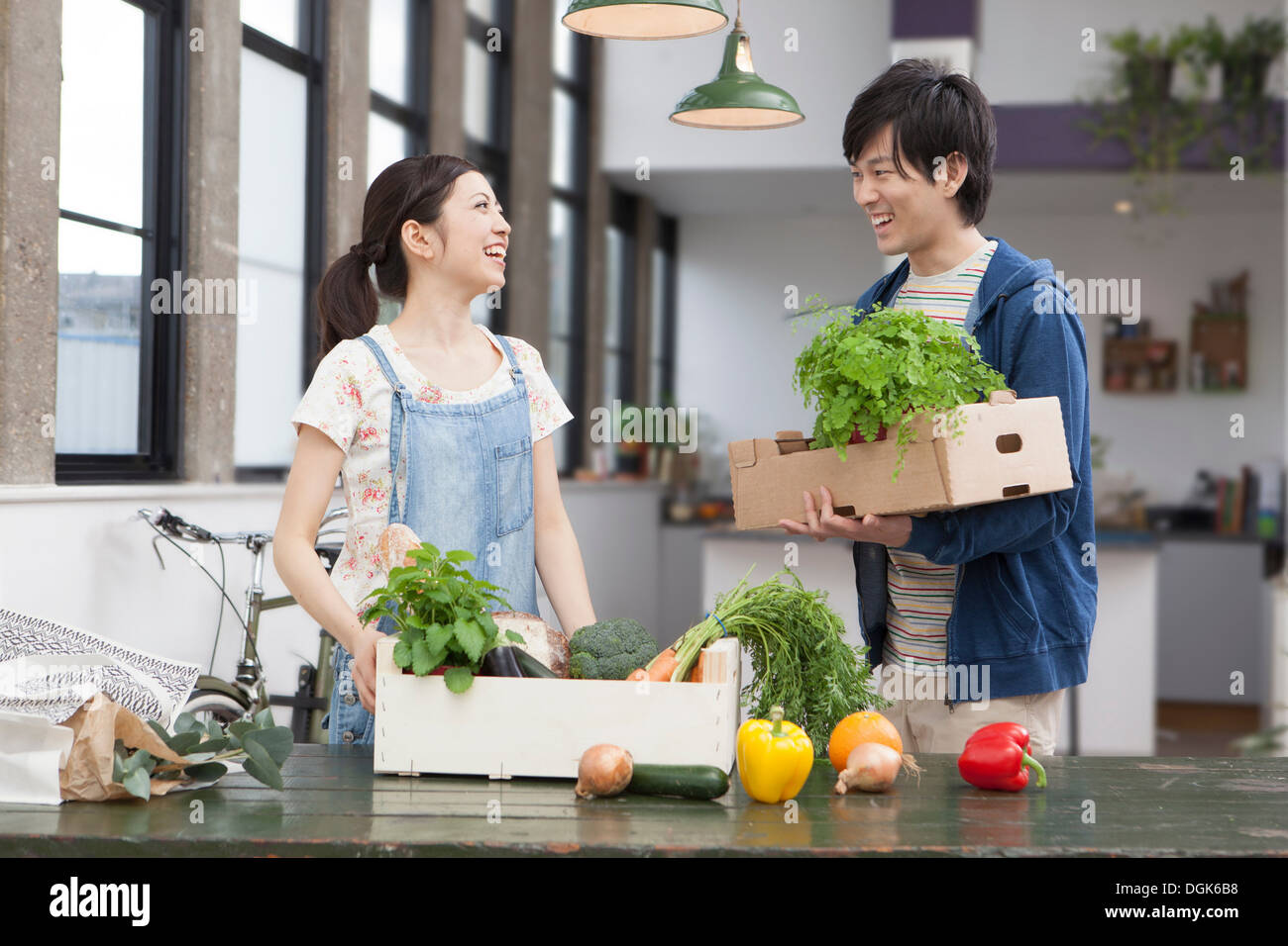Portrait of young couple in kitchen with herbs and vegetables - Stock Image