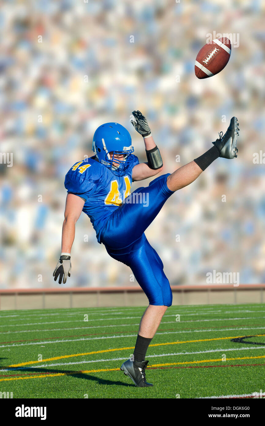 American footballer kicking ball - Stock Image