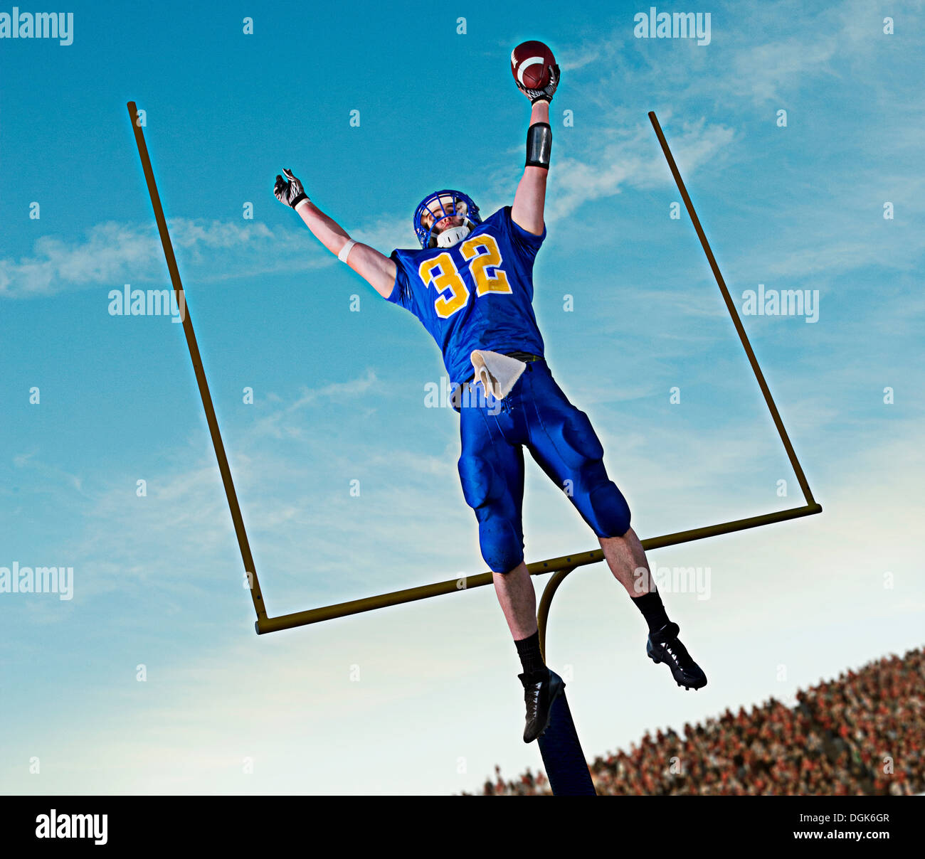American footballer jumping to catch ball in front of goal - Stock Image