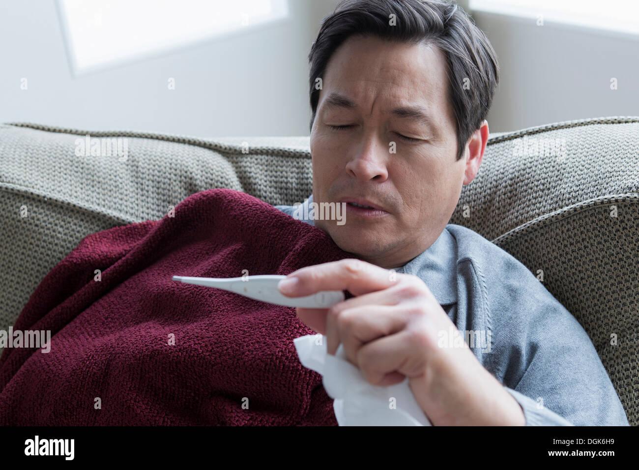 Mature man taking temperature - Stock Image