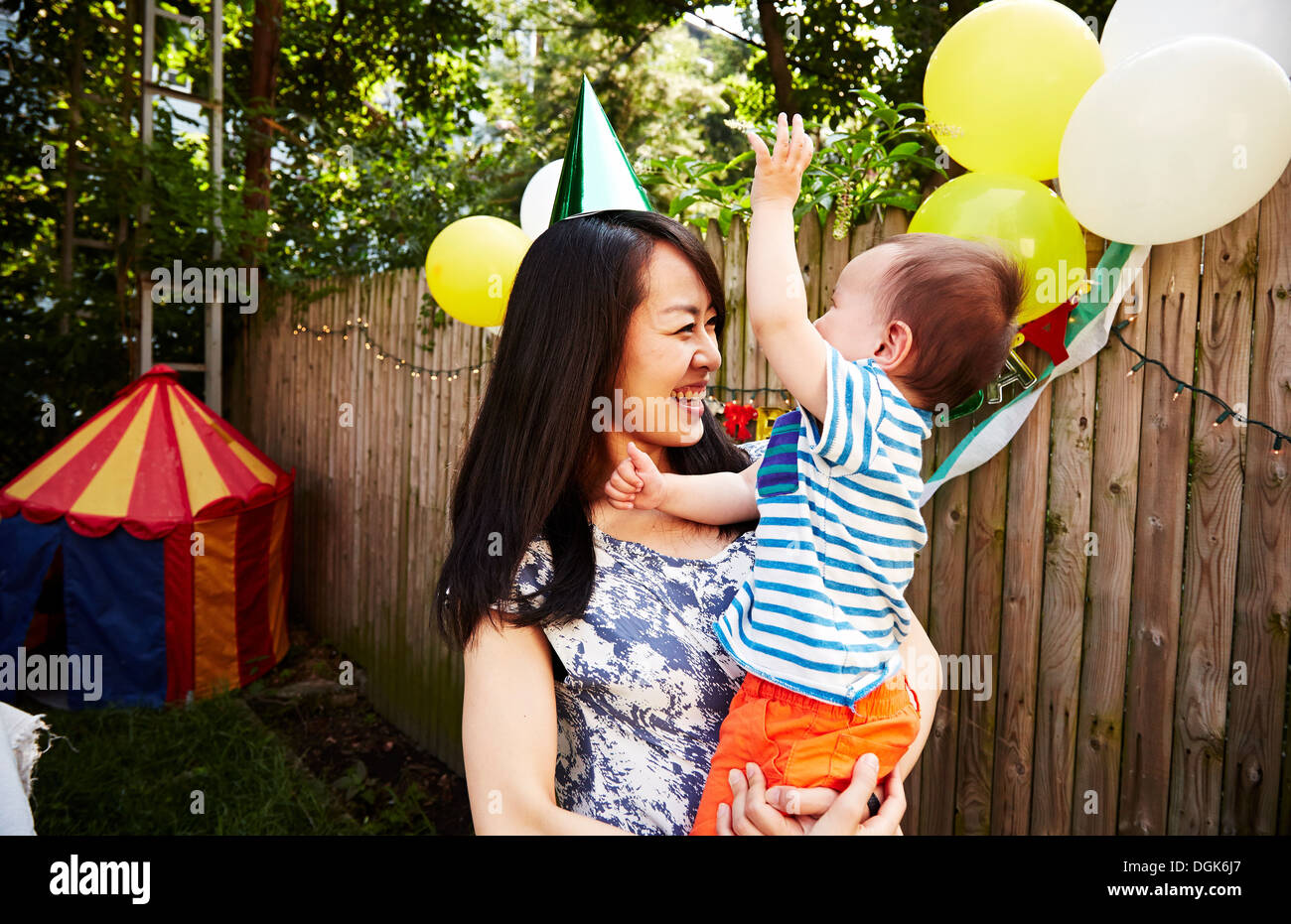 Mother wearing party hat holding baby boy at birthday party - Stock Image