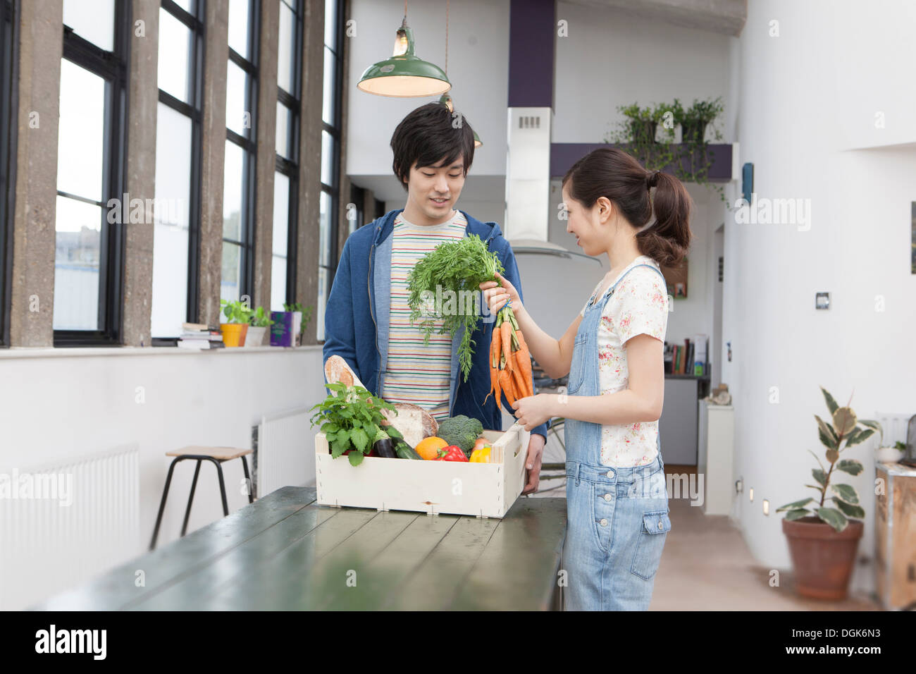 Young couple in kitchen with box of vegetables holding carrots - Stock Image