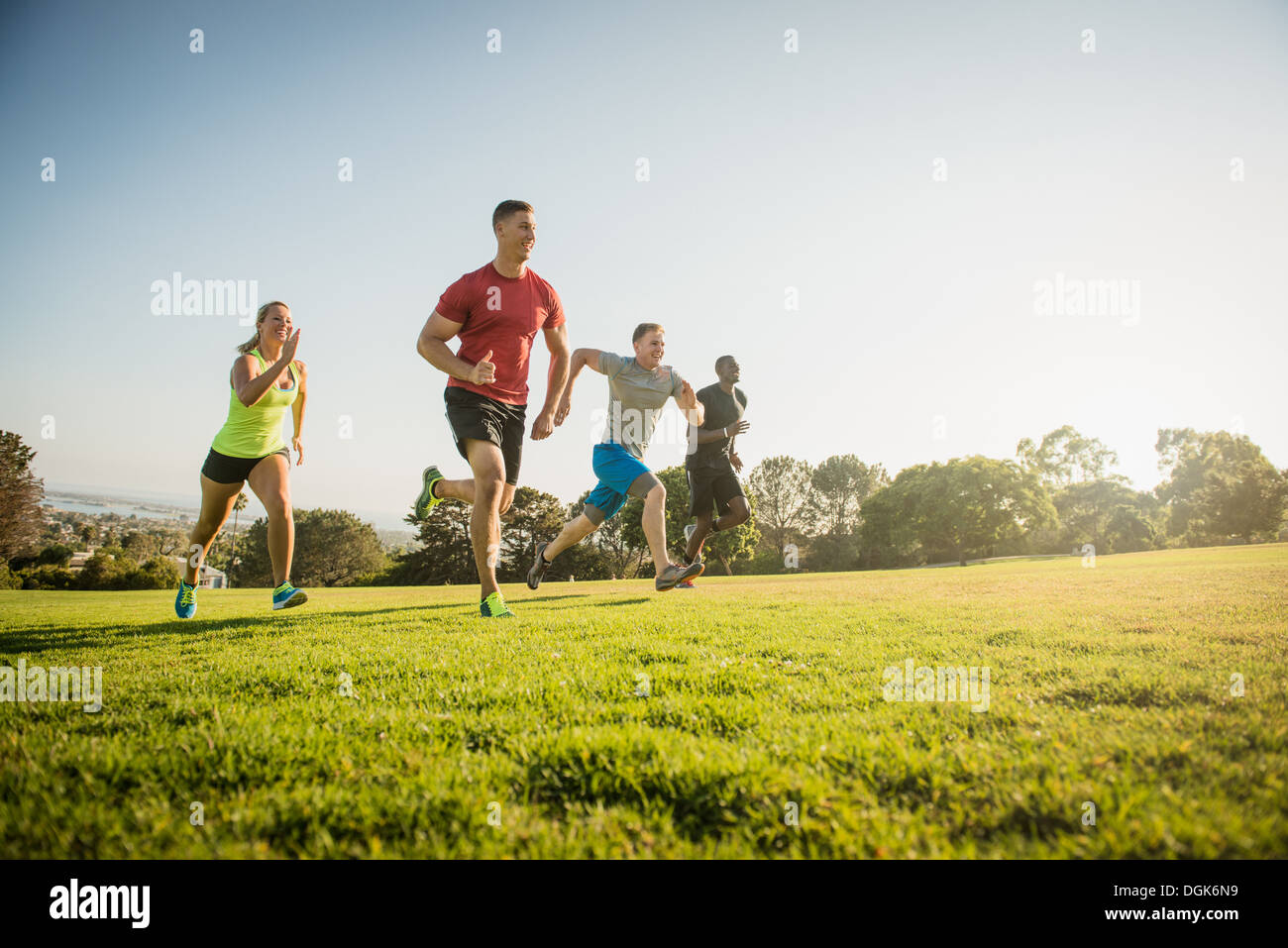 Group of young adults on training run in field - Stock Image