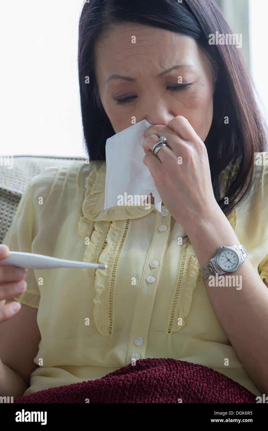 Mature woman taking temperature Stock Photo