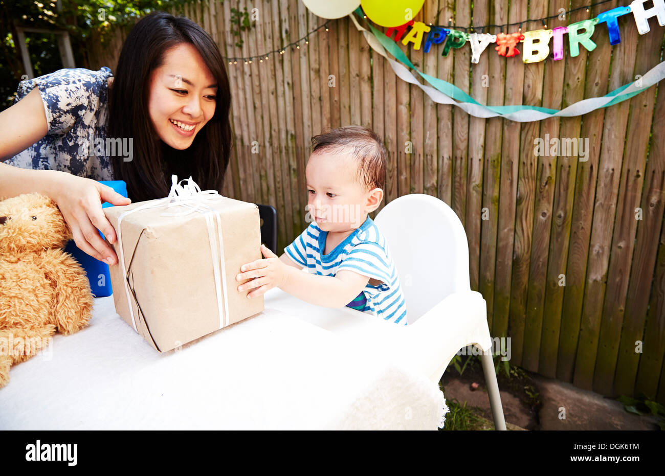 Mother handing birthday gift to baby boy - Stock Image