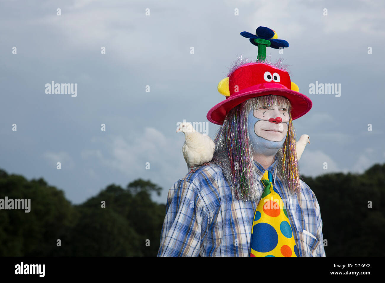 Portrait of clown with doves on shoulders - Stock Image