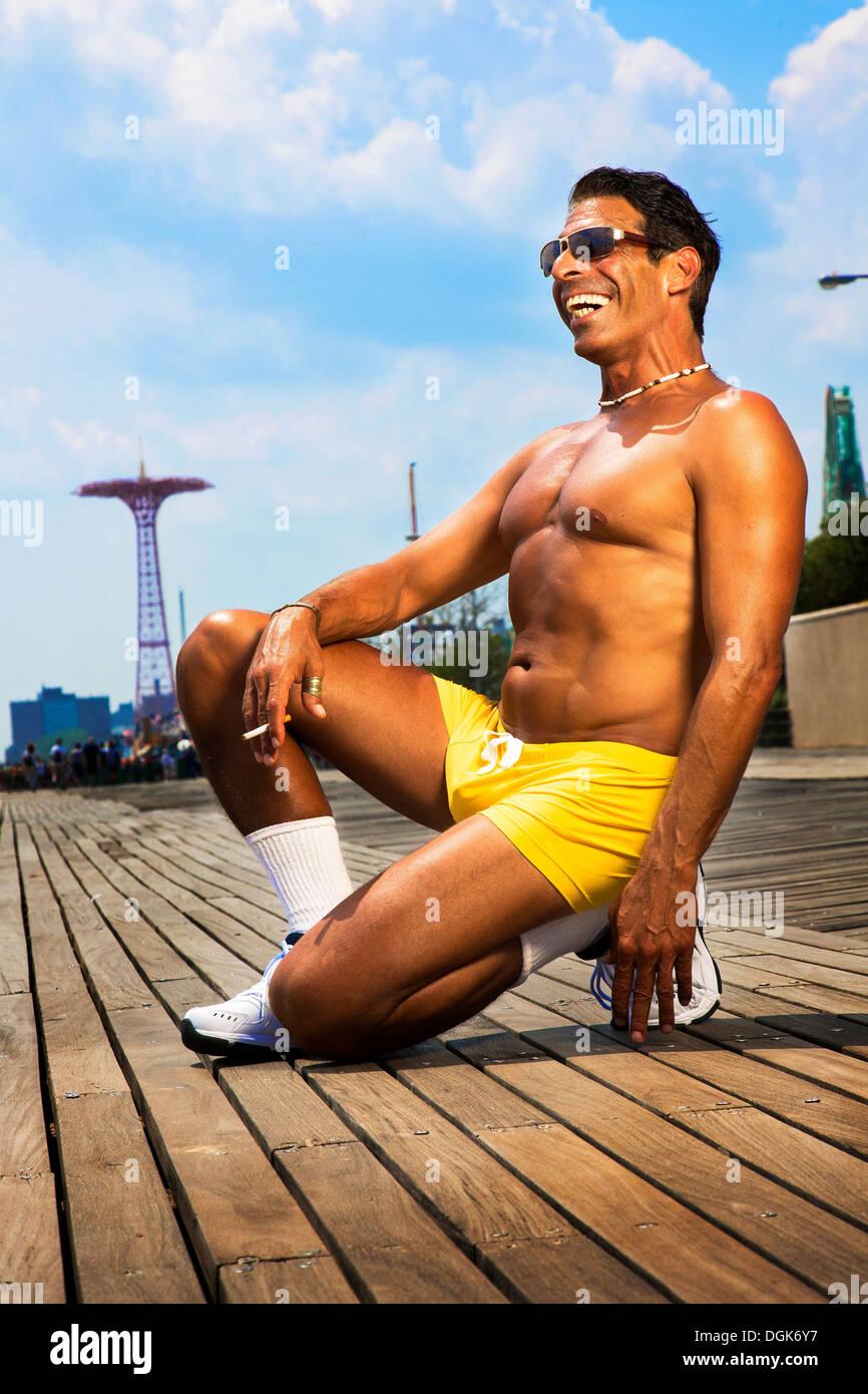 Portrait of man kneeling in yellow trunks, Brooklyn, New York, USA - Stock Image