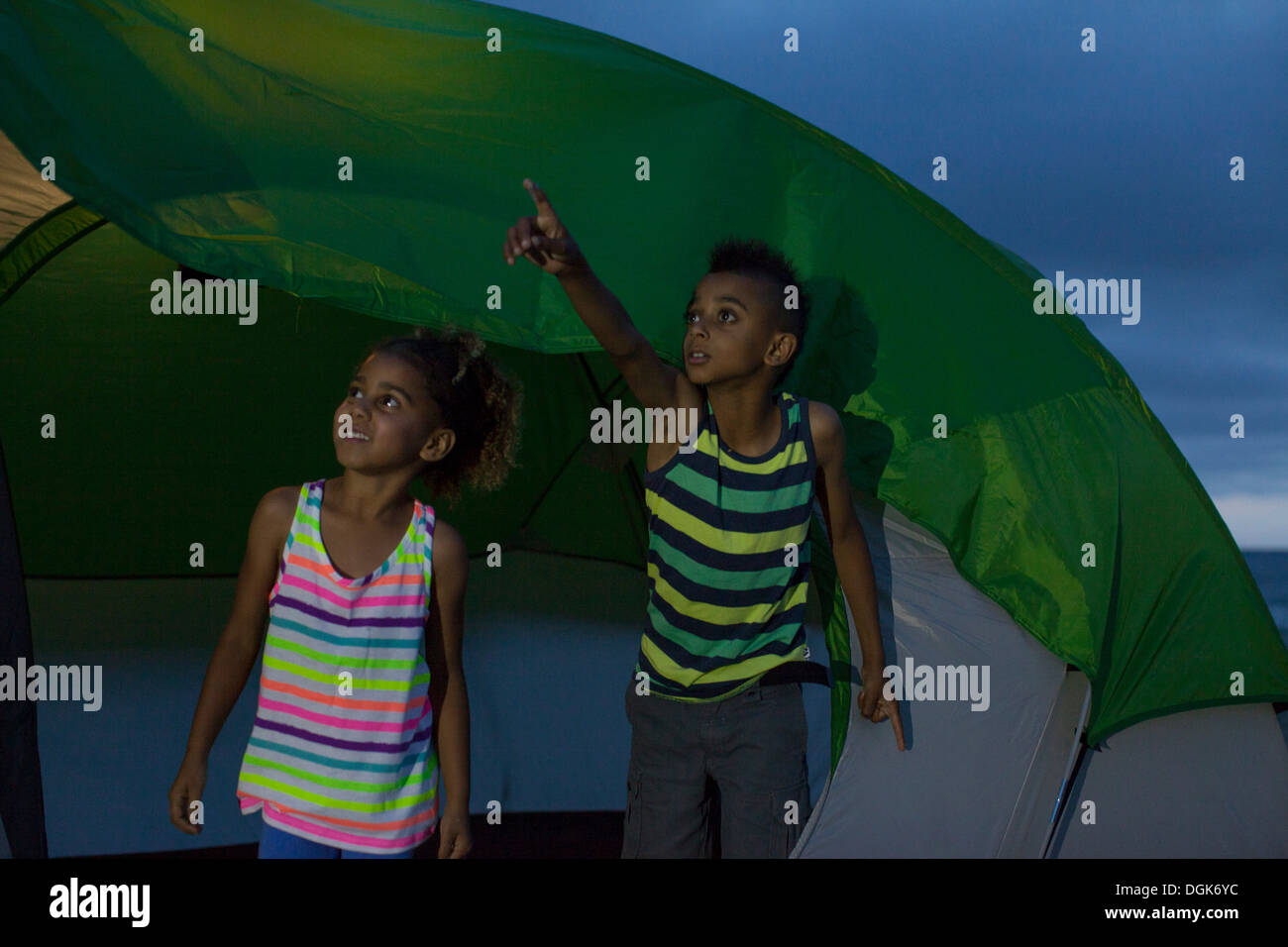 Brother and sister in tent, boy pointing - Stock Image