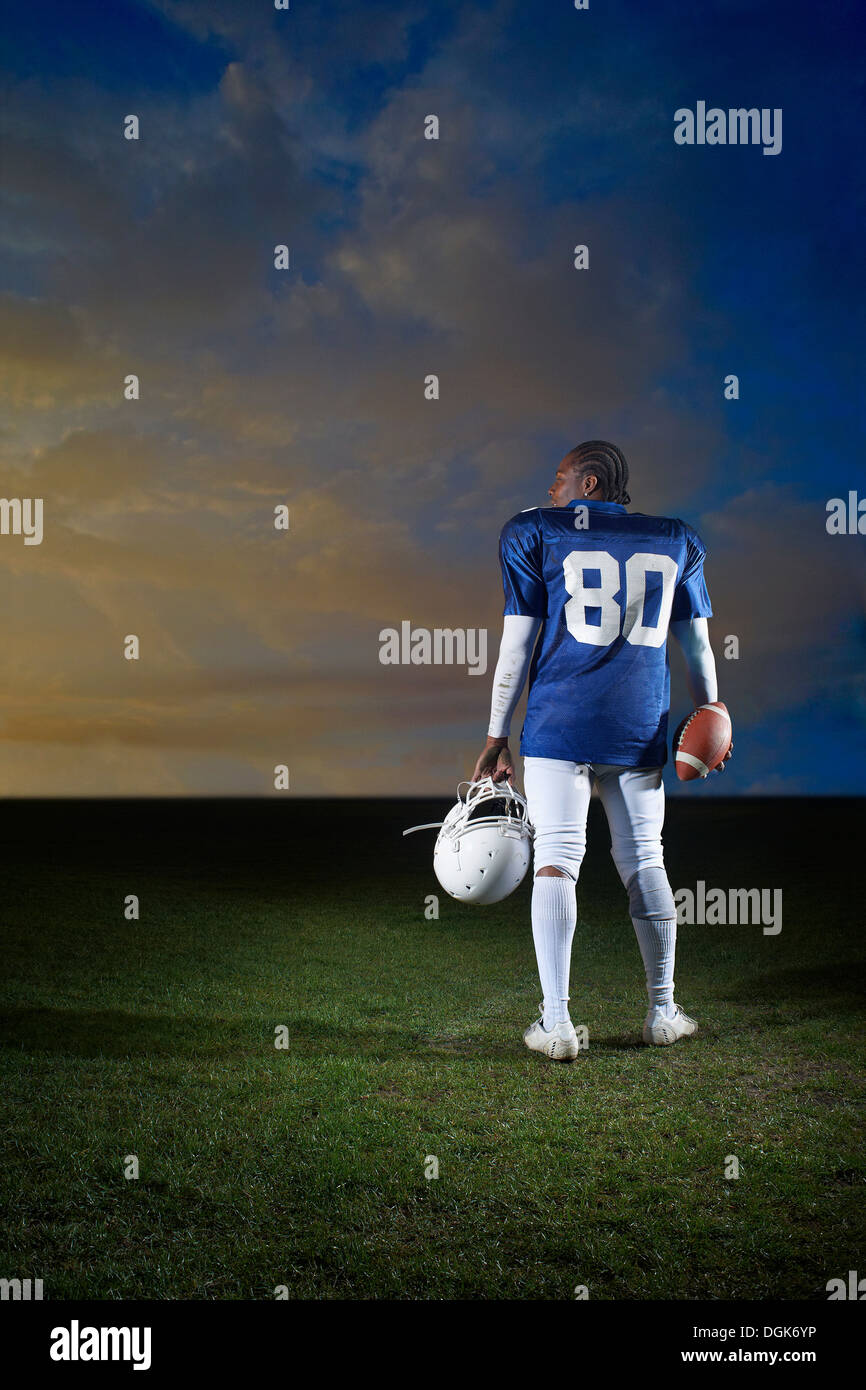 Rear view of American football player holding helmet - Stock Image