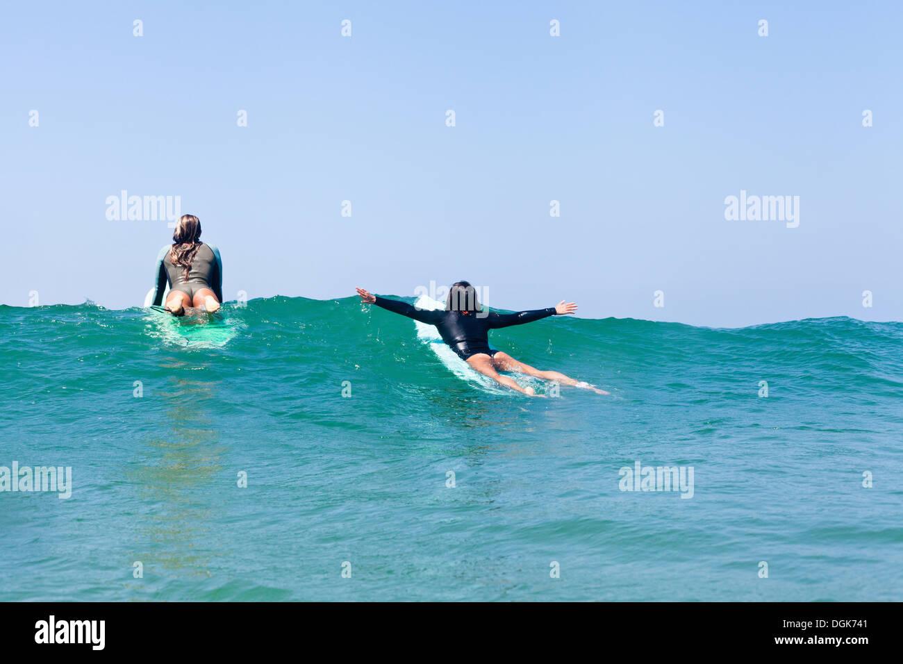 Female friends surfing, Hermosa Beach, California, USA - Stock Image