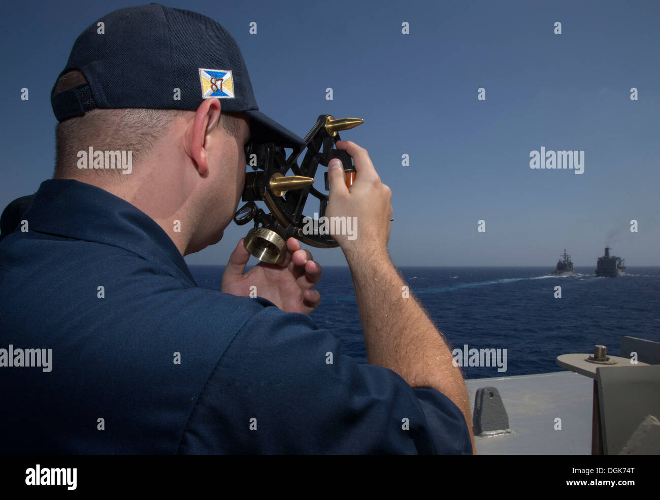 Lt. Matthew Parr uses a sextant aboard the guided-missile destroyer USS Mason (DDG 87) to measure distance while approaching the Military Sealift Command fleet replenishment oiler USNS Laramie (T-AO 203), right, and the guided-missile cruiser USS San Jaci - Stock Image