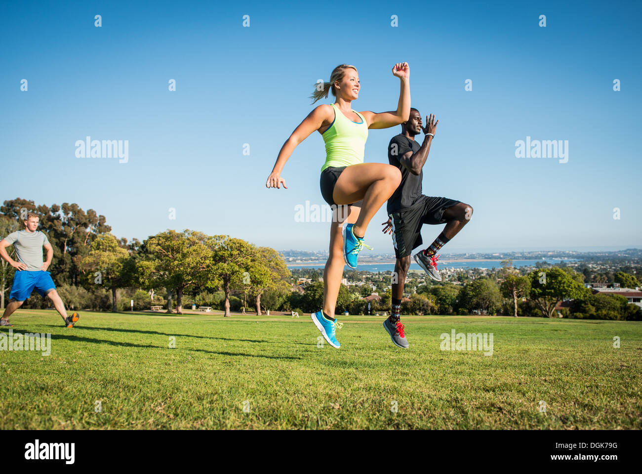 Small group of young adults training in field - Stock Image