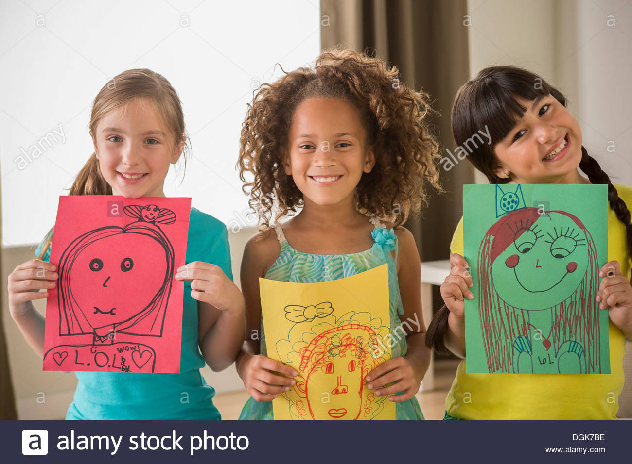 Three girls holding drawings of faces - Stock Image
