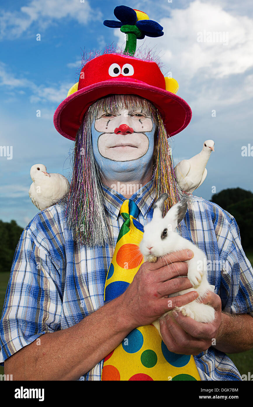Portrait of clown holding a rabbit and with doves on shoulders - Stock Image