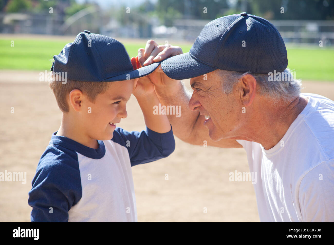 Boy and grandfather in baseball caps, face to face - Stock Image
