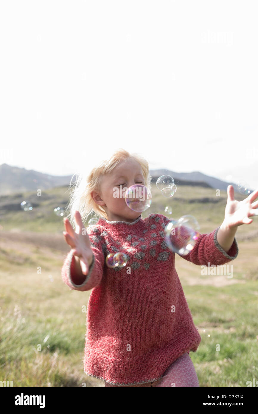 Young girl with eyes closed running to catch bubbles - Stock Image