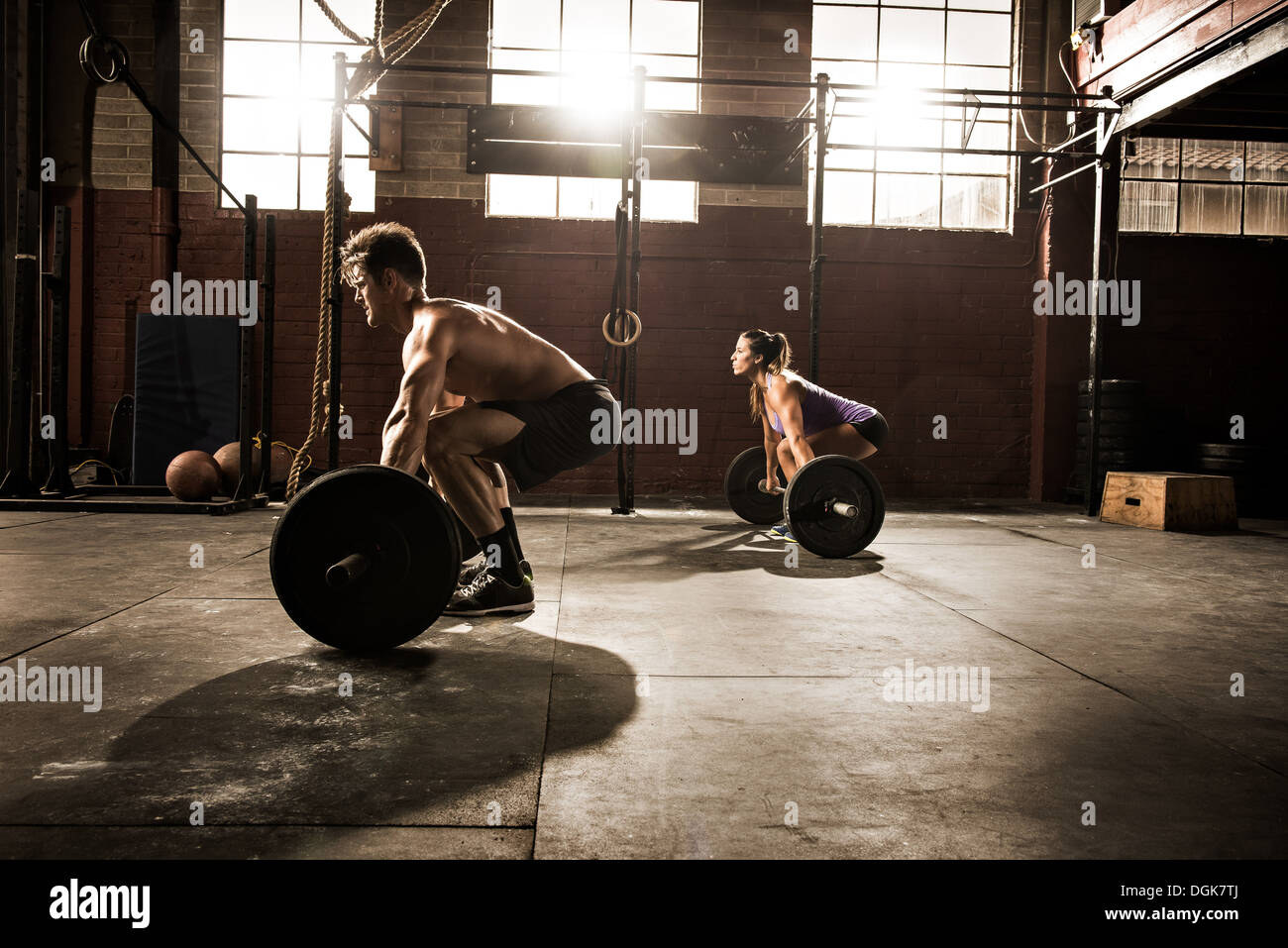 Two young adults working out with barbells in gym - Stock Image
