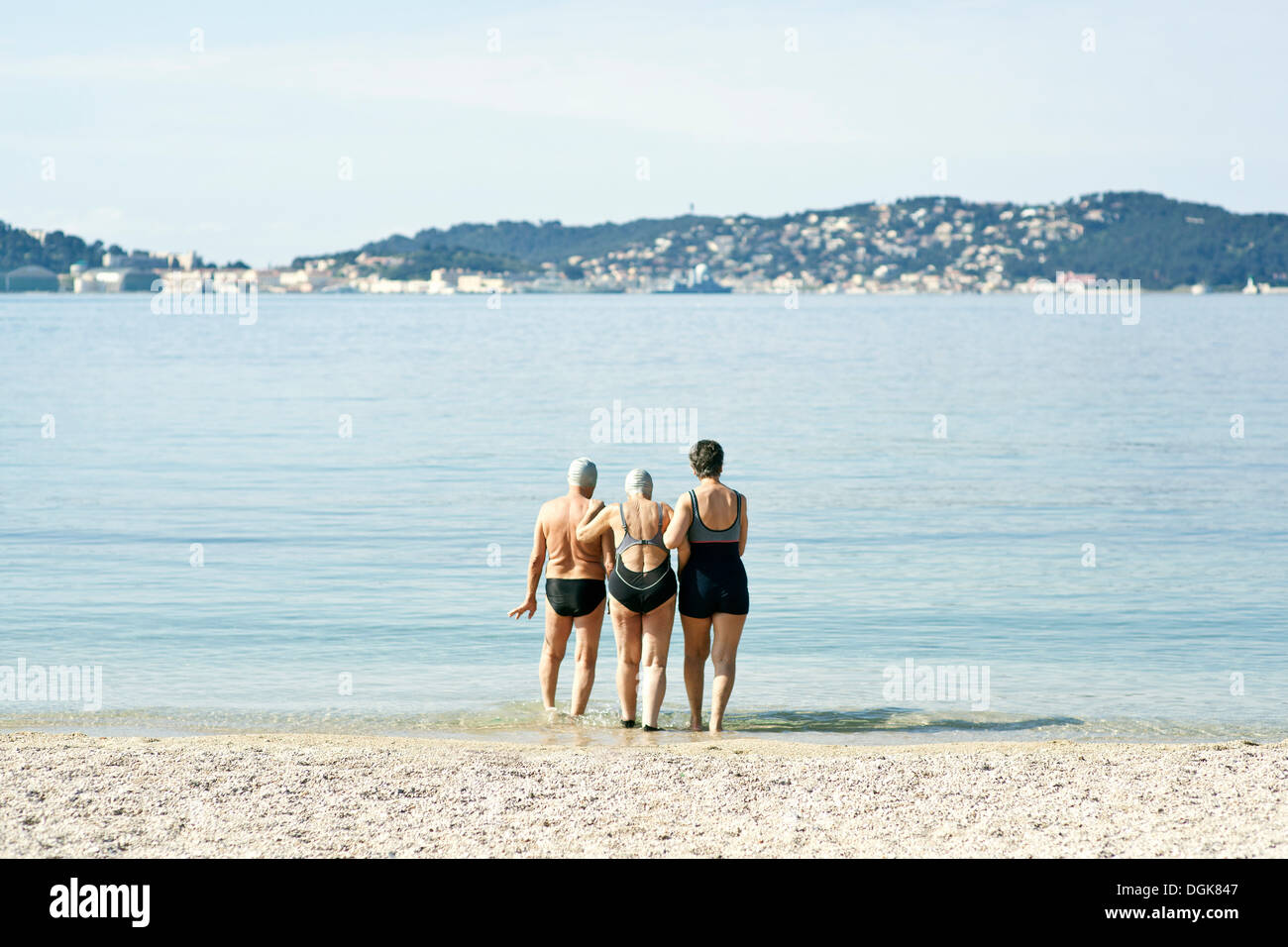Three senior friends walking into the sea, rear view - Stock Image