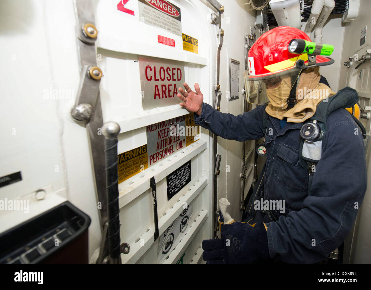 Logistics Specialist 2nd Class Ibarra Botoy inspects the temperature of a hatch during a general quarters drill aboard the Arle - Stock Image