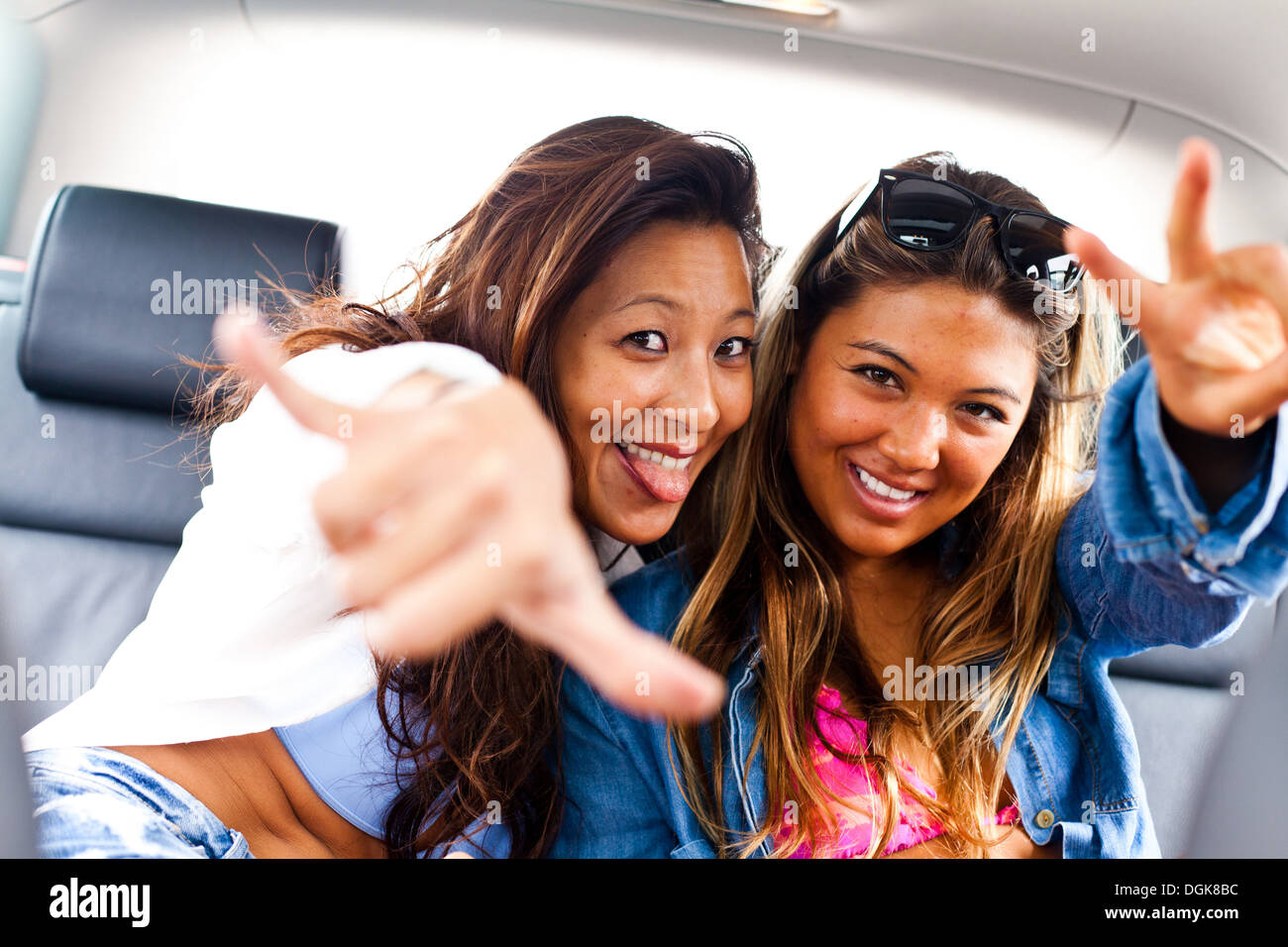 Two female friends making hand gestures in car - Stock Image